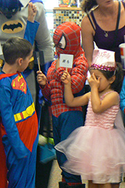 children dressed in comic book character costumes