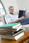 photo of man relaxing in cair reading a book with a stack of books beside him